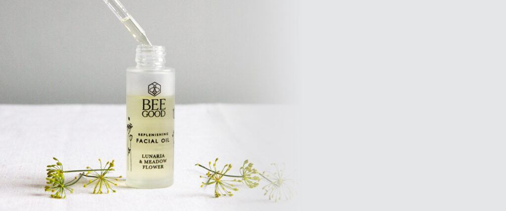bee good replenishing facial oil with plants on white surface