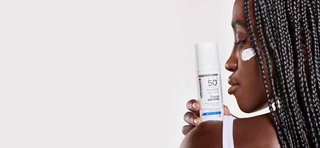 model holding ultrasun product which offers sun protection with skincare benefits